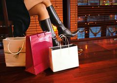 Woman in boots sitting, bags on floor to the side, lower section Stock Photos