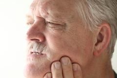 Senior man has jaw or tooth pain Stock Photos