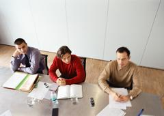 Businessmen sitting at table in office space. Stock Photos