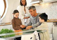 Family of four together in kitchen Stock Photos