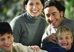 Adult man and woman with two children, head and shoulders, outside, close-up Stock Photos