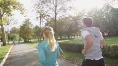 Rear View Shot Of Young Athletic Couple Jogging Through Sunlit Park Stock Footage