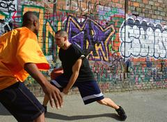 Man dribbling basketball, opponent blocking, next to graffitied wall - stock photo