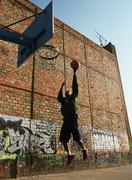 Man going up for a basketball lay-up next to graffitied wall - stock photo