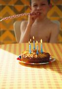 Little boy with birthday cake and party horn blower Stock Photos