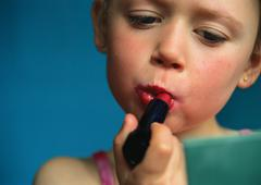 Little girl putting on lipstick, close-up - stock photo