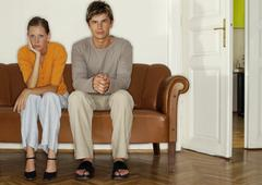 Stock Photo of Man and woman sitting side by side on sofa