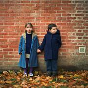 Boy and girl holding hands and making faces in front of brick wall, full length Stock Photos