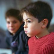 Boy puffing cheeks out, second boy looking at him in background Stock Photos