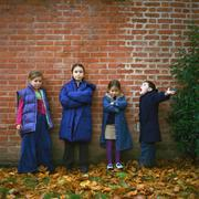 Four children wearing coats in front of brick wall, full length Stock Photos