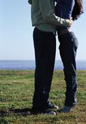 Young couple embracing, waters edge in distance, lower section Stock Photos