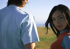 Young woman outdoors with friend, looking at camera, close up Stock Photos