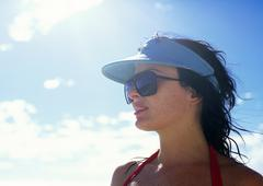 Stock Photo of Woman wearing sunglasses and sun visor outdoors, portrait