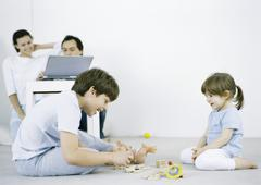 Boy and girl sitting on floor playing, man and woman using laptop in background Kuvituskuvat