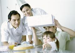 Boy and girl with parents having birthday party - stock photo