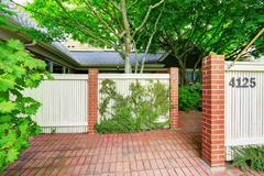 Wooden fence with brick columns and tile floor front yard Stock Photos