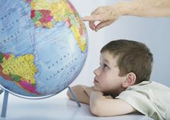 Boy looking at globe, elderly person's hand pointing to spot on globe Stock Photos