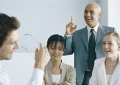 Colleagues having meeting, smiling, one man pointing finger Stock Photos