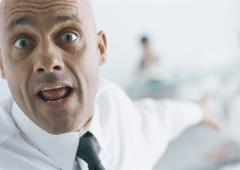 Businessman with eyebrows raised and mouth open pointing into background, - stock photo
