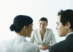 Man and woman smiling at each other, sitting across from smiling businesswoman Stock Photos