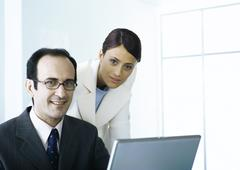 Businessman and businesswoman with laptop looking at camera Stock Photos