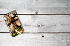 Modern mobile device showing mussels on top of an old wooden table Kuvituskuvat