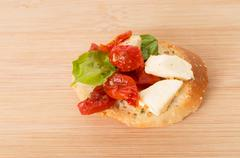 bruschetta with olive oil, sundried tomatoes, mozarella and fresh basil  on   - stock photo