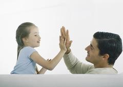 Man and girl playing hand-clapping game - stock photo
