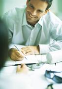 Man smiling while writing in agenda, looking at second person Stock Photos