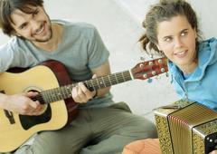 Young man playing guitar, young woman playing accordion - stock photo