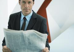 Businessman holding newspaper, looking at camera Stock Photos
