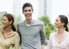 Three friends laughing in urban park Stock Photos