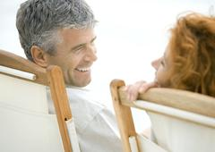 Mature couple, sitting in deck chairs, smiling at each other Stock Photos