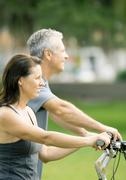 Mature couple on bikes, cropped Stock Photos