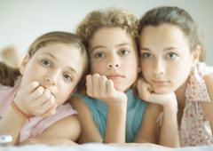 Preteen girls leaning on elbows, looking out of frame Stock Photos