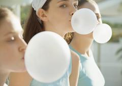 Preteen girls blowing bubbles with chewing gum - stock photo