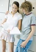 Teenage couple leaning against lockers, talking about school work Stock Photos