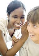 Teen girl whispering to teen boy Stock Photos