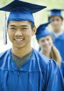 Graduates standing in line, focus on young man in foreground Stock Photos