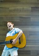 Boy playing guitar and singing with emotion Kuvituskuvat
