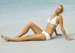 Woman lounging on beach in sun, full length Stock Photos