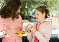 Two preteen girls eating junk food Stock Photos