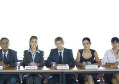 Executives sitting at conference table, looking at camera Stock Photos
