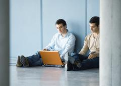 Two young businessmen, sitting on floor, using laptop Stock Photos