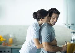 Woman kissing man from behind in the kitchen Stock Photos