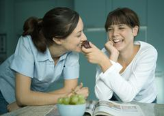 Mother eating fruit from daughter's hand Stock Photos