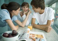 Woman and teenage children standing in kitchen Stock Photos