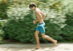 Boy in swimming trunks running Stock Photos