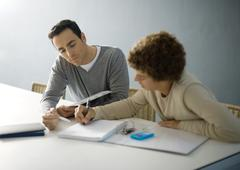 Father helping teenage son with homework Stock Photos