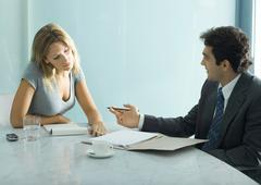 Professional man and woman speaking and looking over document at table Stock Photos